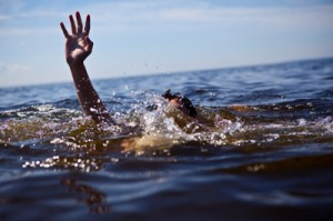 photo of a man drowning with a hand reaching out of the water - powerlessness