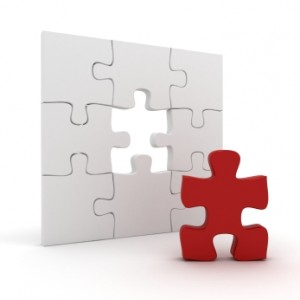 image of a white puzzle missing one red piece, which is detached from the puzzle resting in front - detaching is not abandoning - no more enabling